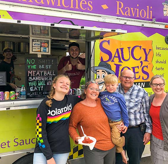 Happy family smiling with Saucy Joe's employees at home retirement party