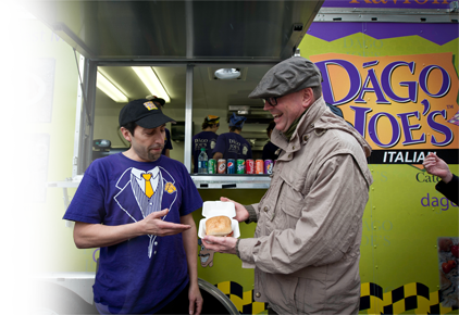 Saucy Joe presenting his sandwich to a happy customer.